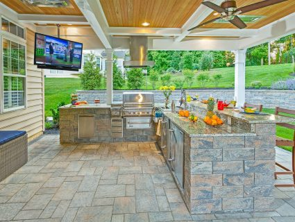 An outdoor kitchen containing a stone bar complete with a grill and large television mounted overhead