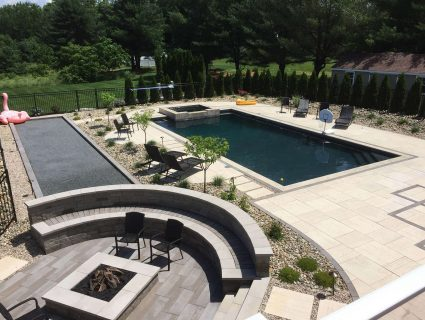 An in-ground pool surrounded by hardscape with a fire pit and chairs