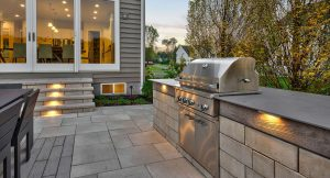 An outdoor kitchen with a stainless teel grill on a stone patio