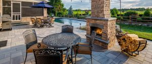 An outfoor fireplace on a stone patio that surrounds a pool with chairs and a table