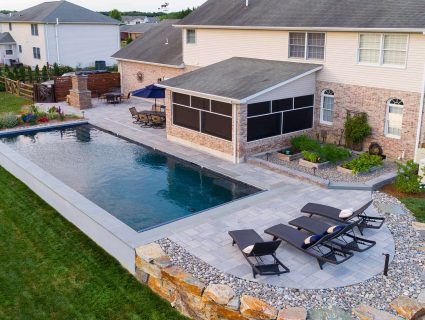 An in-ground pool surrounded by a hardscaped patio with lounge chairs