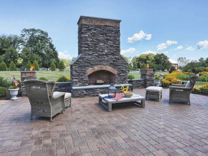 A stone patio with an outdoor fireplace in the center surrounded by chairs