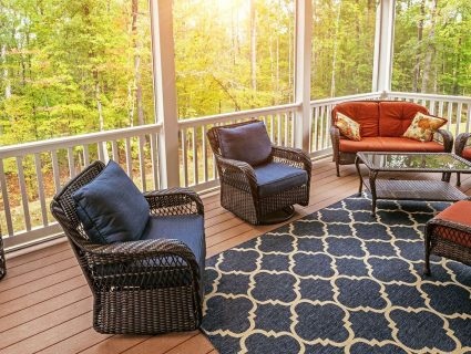 A screened-in porch containing tables and chairs with a view of nearby woods