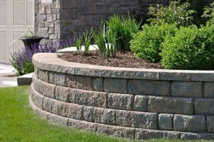 A retaining wall holding green grasses and shrubs