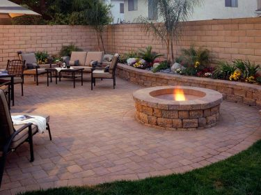 A stone patio with a lit firepit