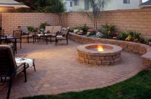 A hardscape patio with a table and chairs placed next to a fire pit