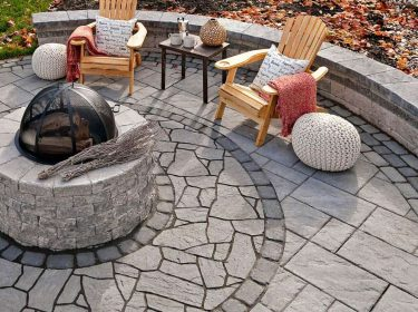 An overhead view of a hardscape patio with a firepit, table and chairs