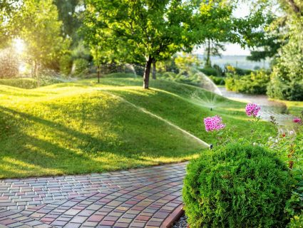 A brick path lined with flowers winding through lush landscaping that is being watered with sprinkers