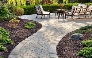 A walkway surrounded by landscaping leading to a patio with a table and chairs