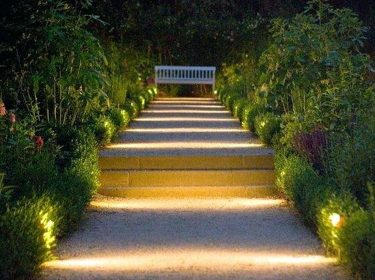 A walkway at night illuminated with outdoor lighting