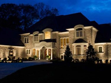 A home exterior at night illuminated with outdoor lighting
