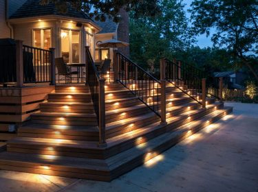 A deck staircase with each step illuminated with a small light