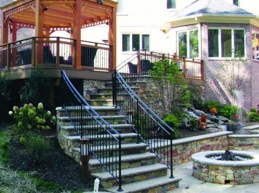 A stone patio with stairs that have an iron railing