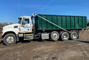 A flat bed truck transporting a roll-off dumpster