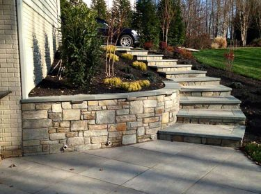 A stone stairway leading down to a driveway