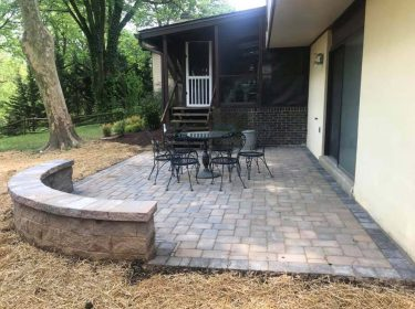 A stone patio with a retaining wall