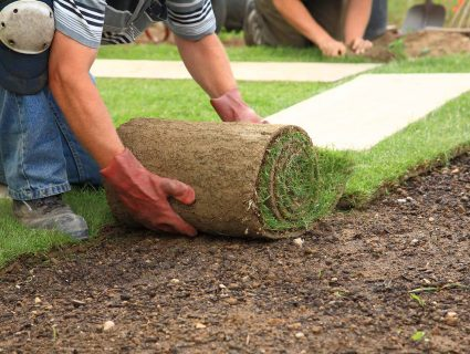 A man laying sod while wearing kneepads and gloves