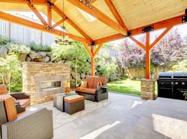 An exterior covered patio with a fireplace and furniture