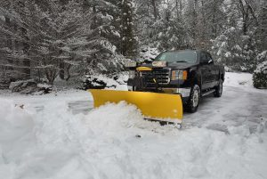 A snow plow clearing a parking lot after a storm